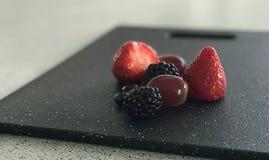 Φράουλες, βατόμουρα και σταφύλια στον τεμαχίζοντας πίνακα με το θολωμένο υπόβαθρο Στοκ Εικόνες