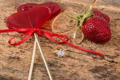 Φράουλες, διαμορφωμένα καρδιά καραμέλες και δαχτυλίδι διαμαντιών Στοκ Φωτογραφίες