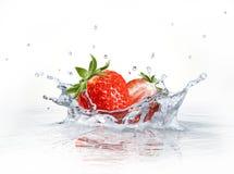 Φράουλες που περιέρχονται στο σαφές νερό, που διαμορφώνει έναν παφλασμό κορωνών. Στοκ Φωτογραφία