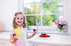 Φράουλες πλύσης μικρών κοριτσιών στην άσπρη κουζίνα Στοκ εικόνα με δικαίωμα ελεύθερης χρήσης