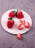 Φράουλες σε έναν τέμνοντα πίνακα Στοκ εικόνες με δικαίωμα ελεύθερης χρήσης