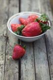 Φράουλες σε ένα κύπελλο στο γκρίζο ξύλινο υπόβαθρο Στοκ Εικόνες
