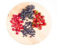 Φράουλες, σμέουρα, βακκίνια και σταφύλια στο ξύλινο πιάτο Στοκ Εικόνα