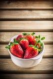 Φράουλες στο άσπρο κεραμικό κύπελλο στον ξύλινο πίνακα Στοκ Φωτογραφία