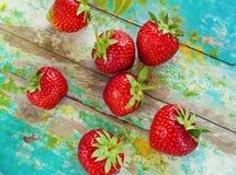 Φράουλες στο εκλεκτής ποιότητας ξύλινο μπλε υπόβαθρο στοκ εικόνες