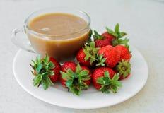 Φράουλες στο φλυτζάνι κύπελλων και καφέ Στοκ Εικόνες