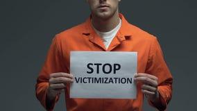 Φράση δίωξης στάσεων στο χαρτόνι στα χέρια του καυκάσιου φυλακισμένου, βία απόθεμα βίντεο