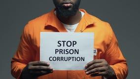 Φράση δωροδοκίας φυλακών στάσεων στο χαρτόνι στα χέρια του μαύρου φυλακισμένου, αναταραχή απόθεμα βίντεο