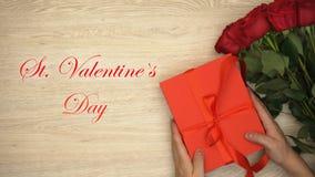 Φράση ημέρας βαλεντίνων του ST, αρσενικά χέρια που βάζει την κοντινή δέσμη κιβωτίων δώρων των τριαντάφυλλων, αγάπη απεικόνιση αποθεμάτων