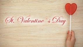 Φράση ημέρας βαλεντίνων του ST στην ξύλινη εκμετάλλευση χεριών υποβάθρου καρδιά-που διαμορφώνεται lollipop απεικόνιση αποθεμάτων
