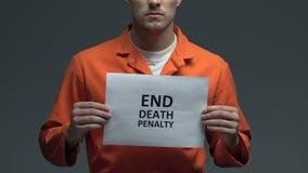 Φράση ποινής του θανάτου τελών στο χαρτόνι στα χέρια του καυκάσιου φυλακισμένου, διαμαρτυρία φιλμ μικρού μήκους