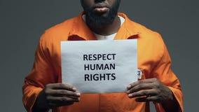 Φράση των ανθρώπινων δικαιωμάτων σεβασμού στο χαρτόνι στα χέρια του αφροαμερικανού φυλακισμένου απόθεμα βίντεο