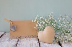 Φρέσκα άσπρα λουλούδια δίπλα στην εκλεκτής ποιότητας κενή κάρτα πέρα από τον ξύλινο πίνακα ο τρύγος φιλτράρισε και τόνισε την εικ Στοκ εικόνα με δικαίωμα ελεύθερης χρήσης
