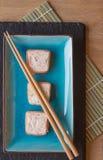 Φρέσκα δέματα τυριών κρέμας σολομών σουσιών στο πιάτο με chopsticks Στοκ Φωτογραφία