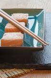 Φρέσκα δέματα τυριών κρέμας σολομών σουσιών στο πιάτο με chopsticks Στοκ φωτογραφία με δικαίωμα ελεύθερης χρήσης