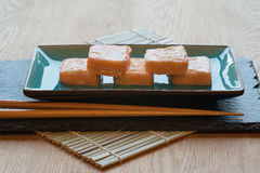 Φρέσκα δέματα τυριών κρέμας σολομών σουσιών στο πιάτο με chopsticks Στοκ Εικόνες