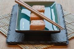 Φρέσκα δέματα τυριών κρέμας σολομών σουσιών στο πιάτο με chopsticks Στοκ Φωτογραφίες