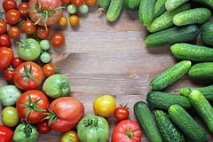 Φρέσκα αγγούρια, κόκκινες και πράσινες ντομάτες σε έναν πίνακα Στοκ Φωτογραφία