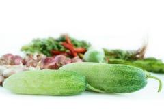 Φρέσκα αγγούρια με το λαχανικό στο υπόβαθρο στοκ φωτογραφία