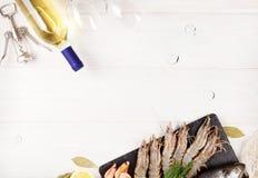 Φρέσκα ακατέργαστα θαλασσινά με τα καρυκεύματα και το άσπρο μπουκάλι κρασιού Στοκ Εικόνες