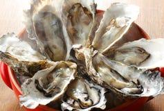 Φρέσκα ακατέργαστα θαλασσινά στρειδιών στον ξύλινο πίνακα Στοκ Εικόνες