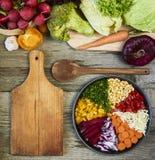 Φρέσκα ακατέργαστα λαχανικά με τον τέμνοντα πίνακα στην ξύλινη σπόλα υποβάθρου στοκ εικόνες με δικαίωμα ελεύθερης χρήσης