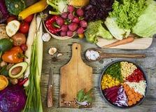Φρέσκα ακατέργαστα λαχανικά με τον τέμνοντα πίνακα στην ξύλινη σπόλα υποβάθρου στοκ φωτογραφίες
