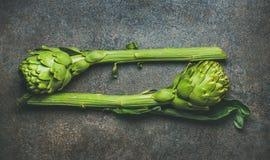 Φρέσκα ακατέργαστα πράσινα artichockes πέρα από το σκοτεινό καφετί υπόβαθρο πετρών Στοκ φωτογραφία με δικαίωμα ελεύθερης χρήσης