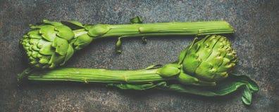 Φρέσκα ακατέργαστα πράσινα artichockes πέρα από το σκοτεινό υπόβαθρο πετρών Στοκ εικόνες με δικαίωμα ελεύθερης χρήσης