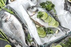 Φρέσκα ακατέργαστα ψάρια τσιπουρών που μαγειρεύουν μαύρο countertop πετρών, τοπ άποψη στοκ εικόνες