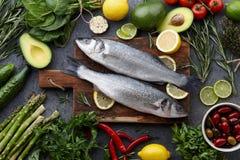 Φρέσκα ακατέργαστα seabass και συστατικά για το μαγείρεμα στοκ εικόνα