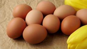 Φρέσκα αυγά σε καφετί τυλίγοντας χαρτί Αυγά και τουλίπες απόθεμα βίντεο