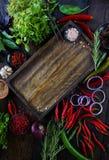 Φρέσκα λαχανικά, καρυκεύματα και χορτάρια στον ξύλινο πίνακα και τον κενό τέμνοντα πίνακα Στοκ φωτογραφία με δικαίωμα ελεύθερης χρήσης