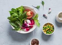 Φρέσκα λαχανικά - ραδίκια, ντομάτες, χορτάρια κήπων και πράσινα μπιζέλια και chickpeas σε ένα ανοικτό μπλε υπόβαθρο πετρών Στοκ Εικόνες