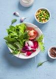 Φρέσκα λαχανικά - ραδίκια, ντομάτες, χορτάρια κήπων και πράσινα μπιζέλια και chickpeas σε ένα ανοικτό μπλε υπόβαθρο πετρών Στοκ εικόνα με δικαίωμα ελεύθερης χρήσης