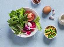 Φρέσκα λαχανικά - ραδίκια, ντομάτες, χορτάρια κήπων, πράσινα μπιζέλια, chickpeas και αυγό σε ένα ανοικτό μπλε υπόβαθρο πετρών Στοκ Φωτογραφία