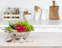 Φρέσκα λαχανικά στον ξύλινο πίνακα πέρα από το θολωμένο αντίθετο εσωτερικό κουζινών Στοκ Εικόνα