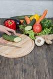 Φρέσκα λαχανικά στον τεμαχίζοντας πίνακα και το σκοτεινό πίνακα Κολοκύθια που κόβονται στα κομμάτια, έναν ξύλινο πίνακα που γίνετ Στοκ εικόνες με δικαίωμα ελεύθερης χρήσης
