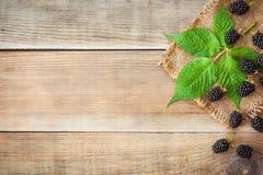 Φρέσκα βατόμουρα με τα φύλλα στο ξύλινο υπόβαθρο στο αγροτικό ύφος Στοκ Φωτογραφία