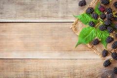 Φρέσκα βατόμουρα με τα φύλλα στο ξύλινο υπόβαθρο στο αγροτικό ύφος Στοκ εικόνες με δικαίωμα ελεύθερης χρήσης