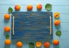 Φρέσκα βερίκοκα γύρω από τον ξύλινο πίνακα Στοκ Φωτογραφίες