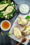 Φρέσκα γλυκά σαλάτα και bruschetta αχλαδιών με το τυρί εξοχικών σπιτιών, ξύλο καρυδιάς στο λευκό πίνακα Στοκ Φωτογραφία