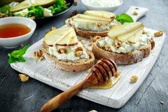 Φρέσκα γλυκά σαλάτα και bruschetta αχλαδιών με το τυρί εξοχικών σπιτιών, ξύλο καρυδιάς στο λευκό πίνακα Στοκ φωτογραφίες με δικαίωμα ελεύθερης χρήσης