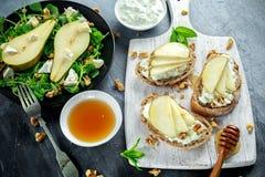 Φρέσκα γλυκά σαλάτα και bruschetta αχλαδιών με το τυρί εξοχικών σπιτιών, ξύλο καρυδιάς στο λευκό πίνακα Στοκ Εικόνα