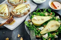 Φρέσκα γλυκά σαλάτα και bruschetta αχλαδιών με το τυρί εξοχικών σπιτιών, ξύλο καρυδιάς στο λευκό πίνακα Στοκ φωτογραφία με δικαίωμα ελεύθερης χρήσης
