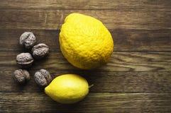 Φρέσκα λεμόνια και καρύδια στο ξύλινο backround, συστατικά, fres στοκ εικόνες