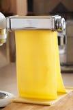 Φρέσκα ζυμαρικά αυγών που κυλιούνται στη μηχανή ζυμαρικών Στοκ Εικόνα