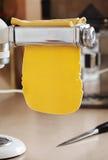 Φρέσκα ζυμαρικά αυγών που κυλιούνται στη μηχανή ζυμαρικών Στοκ Εικόνες