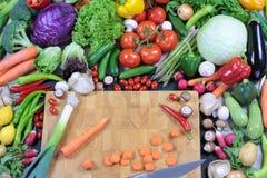 Φρέσκα ζωηρόχρωμα λαχανικά με τον τεμαχίζοντας πίνακα Στοκ Εικόνα