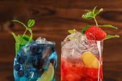 Φρέσκα ζωηρόχρωμα κοκτέιλ με τη μέντα, τον ασβέστη, τον πάγο και τα μούρα στο ξύλινο υπόβαθρο Δύο αναζωογονώντας θερινά ποτά διάσ Στοκ Εικόνες